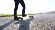 Hipster skateboarder skating on mountain road video