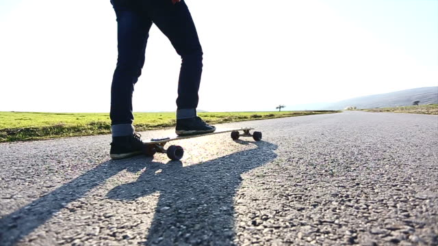 Hipster skateboarder skating on mountain road video