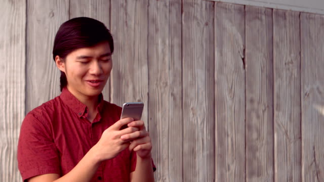 Hipster smiling while using mobile phone video