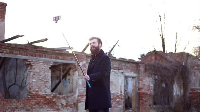 Hipster style bearded man taking selfie with selfie stick video