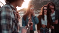 Hipster teen friends having fun with guitar on road trip video