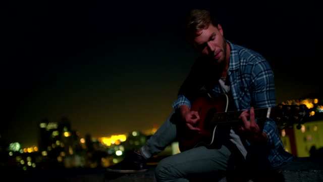 Hipster teenager boy plays guitar sitting on rooftop at night video