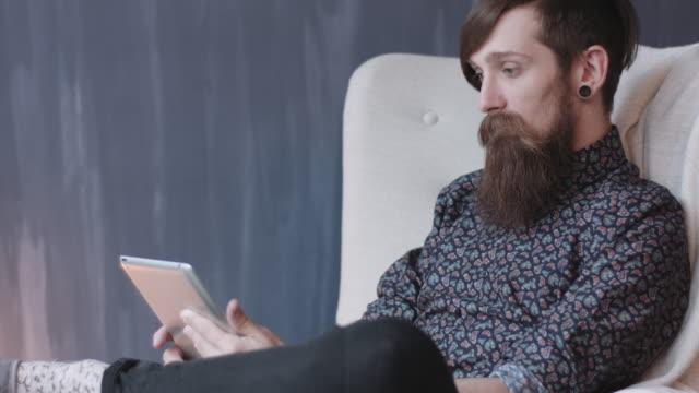 Hipster using digital tablet. video