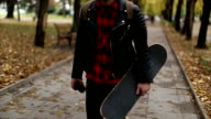 Hipster with skateboard walking video