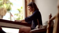 Hipster Woman Typing Computer at Window Seat in Coffee Shop video