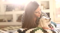 Hipster woman with tattoo playing with her puppy while lying on the floor video