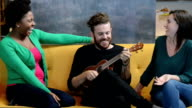 Hipsters Playing Ukulele on Yellow Sofa video
