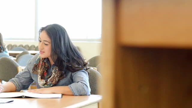 Hispanic adult male and female students studying together at table in college library video