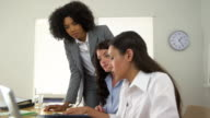 Hispanic, African, and Caucasian business women working together at computer video