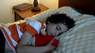 Hispanic child sleeping with his favorite toy video