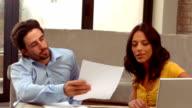 Hispanic couple calculating their accounts video