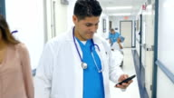 Hispanic doctor checking smart phone in hospital hallway video