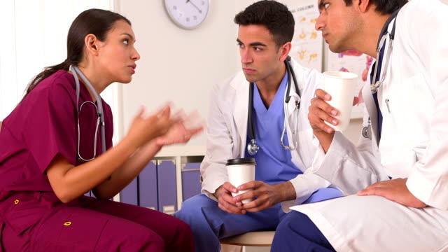 Hispanic doctor talking with her colleagues video