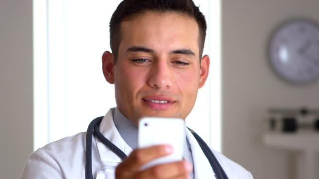 Hispanic doctor using smartphone video