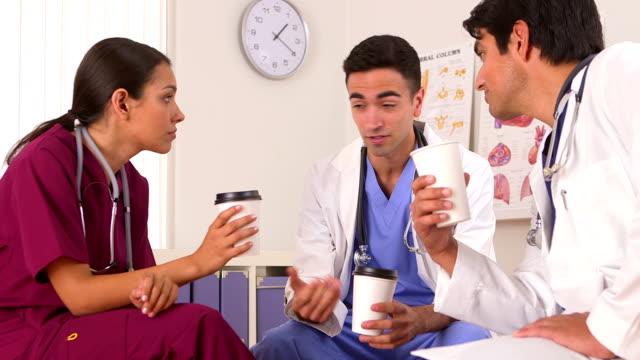 Hispanic doctors talking on their coffee break video