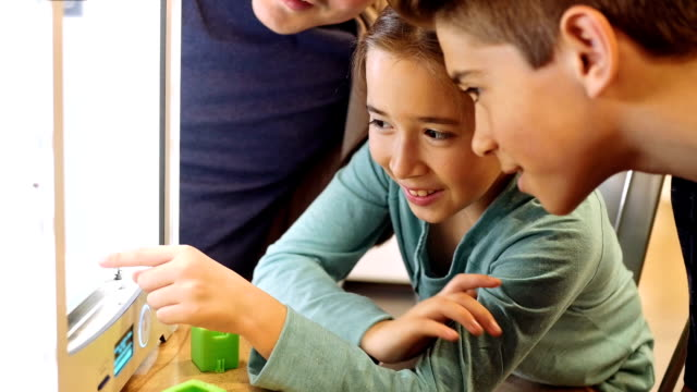 Hispanic elementary age girl and Hispanic preteen boy watch as object prints out on 3D printer video
