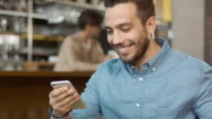 Hispanic Ethnicity Young Man using Mobile Phone at Cozy Coffee Shop. video