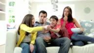 Hispanic Family Sitting On Sofa Watching TV Together video