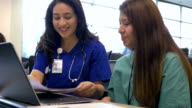Hispanic female professor of nursing tutoring young adult college student video