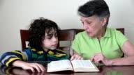Hispanic grandmother and grandson studying the Bible video