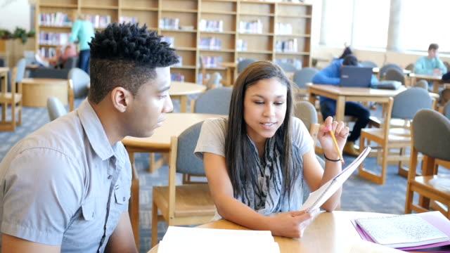 Hispanic high school girl tutoring male African American classmate in library video