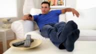 Hispanic man leaning back and watching TV video