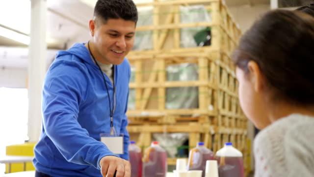 Hispanic man volunteering in food bank, serving meals to children in line video