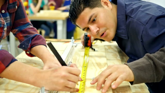 Hispanic mid adult man teaches a woman how to measure a piece of wood in community woodworking shop video