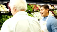 Hispanic mid-adult male grocery store employee is assisting senior Caucasian male customer in produce section of grocery store video