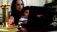 Hispanic mom working at her home office video