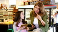 Hispanic mother and daughter checking grocery list on digital tablet video