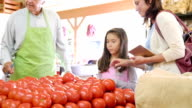Hispanic mother is teaching young daughter about choosing tomatoes at produce market video