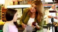 Hispanic mother shopping in produce market video