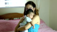 Hispanic mother tapping on back so infant can burp. video