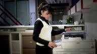 Hispanic secretary makes copies of files video