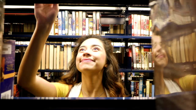 Hispanic teenage home school high school student finds book in local public library video