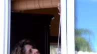 Hispanic Woman Applies Weather Stripping to Kitchen Window Tilt Down video