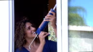 Hispanic Woman Caulks Kitchen Window Closeup video