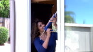 Hispanic Woman Caulks Kitchen Window Tilt Down video