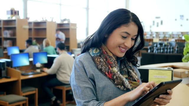 Hispanic woman is using digital tablet in library, looks up and smiles at camera video