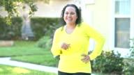 Hispanic woman laughing in front yard video
