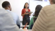 Hispanic woman with tablet teaching adult education class video