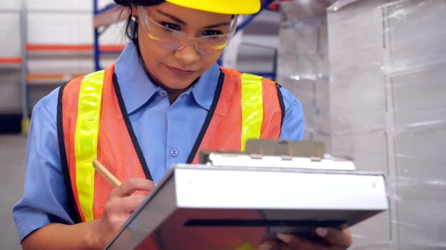 Hispanic woman writing with clipboard in shipping distribution warehouse video