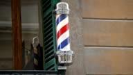 Historic barber pole rotating on a hairdresser shop video