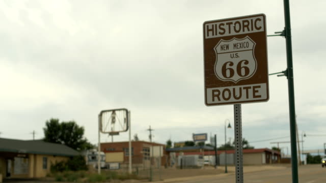Historic Route 66 road sign Santa Rosa, New Mexico with abandoned buildings in the background on a cloudy day. video