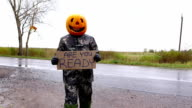Hitchhiking pumpkinhead man hold sign says Are you ready video