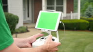 Hobbyist Uses Remote Control for Drone Outside a House Green Screen Tablet video