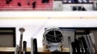 Hockey team's equipment lying on bench, empty ice rink, popular winter sport video