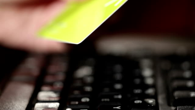 Holding a credit card and typing. video