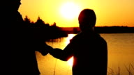 Holding Hand At River Sunset mother and son at sunset near the river video